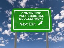 Continuing professional development. Green highway sign with text continuing professional development next exit in white with directional arrow against blue sky Royalty Free Stock Image