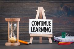 Continue learning. Sandglass, hourglass or egg timer on wooden table. Showing the last second or last minute or time out Stock Image