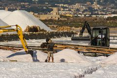 Mountains of salt. Continues the work in the sicilian salt pans immersed in the valleys between sea and mountains Stock Photos