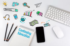 Continuing Education. Computer keyboard and mobile phone on a white table stock photos