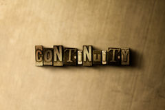 CONTINUITY - close-up of grungy vintage typeset word on metal backdrop Stock Image