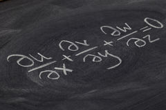 Continuity equation. (mathematical physics) - white chalk handwriting on blackboard stock photography