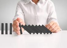 Continuo de los dominós de la parada de la mano derribado Imagen de archivo