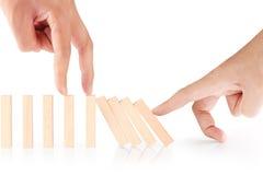 Continuo de los dominós de la parada de la mano derribado Imágenes de archivo libres de regalías