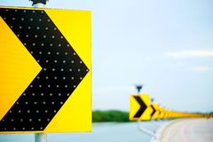 Continuous arrow sign on the curve. Yellow arrow sign reflects the light on the curve and the background has a blurred image of the arrow sign royalty free stock photos