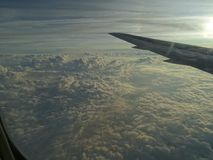 The wing of the plane and clouds at sunset. Continuous clouds under the wing of the aircraft.Sunset from the window.Cumulus clouds.Inversion trace in the sky stock images