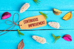 Continuous improvement text on paper tag. With rope and color dried flowers around on blue wooden background stock images