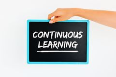 Continuous Learning – text handwritten on chalkboard. In woman hand stock photo