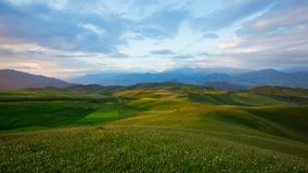 The continuous Qilian mountains at sunset time. Qinghai province of China. There are highland barley fields at the hillside royalty free stock image