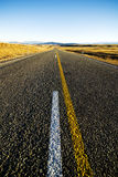 Continuous Road in a Scenic with Mountain Ranges Afar Royalty Free Stock Photography