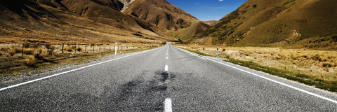 Continuous Road in a Scenic with Mountain Ranges Afar Concept Royalty Free Stock Images