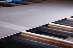 Continuous sheet of metallic material being fed through machine Stock Images