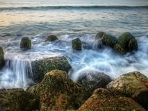 Continuous turning waves on the shore, along the shore are blue-covered rocks royalty free stock images