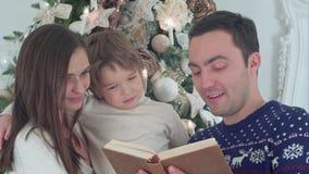 Conto novo do Natal da leitura do pai, quando mãe e seu filho feliz que sussurram secretamente video estoque