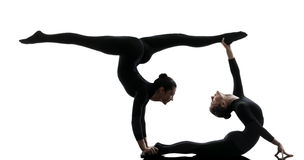 Contorcionista de duas mulheres que exercita a silhueta ginástica da ioga Fotos de Stock
