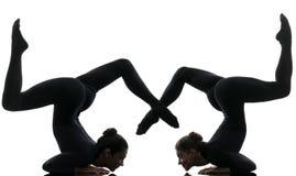 Contorcionista de duas mulheres que exercita a silhueta ginástica da ioga Imagens de Stock