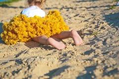 Contorne os saltos luxúrias amarelos dos pés da praia da areia da menina fotos de stock royalty free