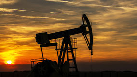 Contorno de funcionamento do poço de petróleo e gás, esboçado no por do sol Imagens de Stock