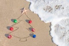 Contorno del árbol de navidad con las decoraciones, la estrella y la onda en la playa Imagenes de archivo
