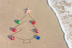 Contorno del árbol de navidad con las decoraciones, la estrella y la onda en la playa Fotografía de archivo