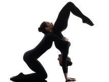Contorsionist 2 женщин работая гимнастический силуэт йоги стоковые изображения rf