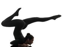 Contorsionista della donna che esercita yoga relativa alla ginnastica   siluetta Fotografie Stock Libere da Diritti