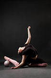 Contortionist with ball. Against dark background Stock Photos