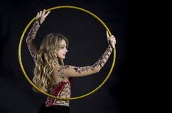The contortionist girl in stage costume with hoops. Studio shot on dark background Royalty Free Stock Photography