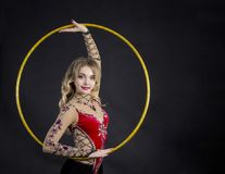 The contortionist girl in stage costume with hoops. Studio shot on dark background Royalty Free Stock Photos
