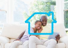 Contour à la maison avec des couples utilisant le comprimé numérique à la maison photos stock