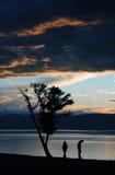 Contour de deux personnes sur le fond du coucher du soleil lumineux Photo stock