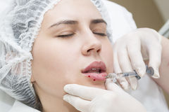 Contour plastic lips. Young girl in a clinic contour lips procedure Stock Photos