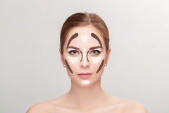 Contouring. Make up woman face on grey background.  Professional Stock Photo