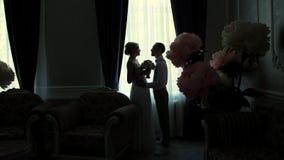 Contours foncés des jeunes mariés vis-à-vis de la fenêtre la fille et le jeune type se tiennent en longueur, faisant face à chacu banque de vidéos