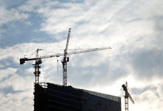 Contours of tower cranes above office building Royalty Free Stock Photography