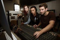 Contrôle d'équipe d'ingénieur du son un bruit sur le mélangeur images libres de droits