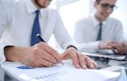 Contrôle d'homme d'affaires au sujet de coût et de faire le rapport de graphique de finances au bureau image libre de droits