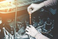 Contrôle de femme l'huile à moteur de la voiture Photographie stock libre de droits