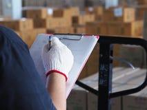 Contrôle de femmes fonctionnant dans l'entrepôt Image stock