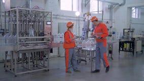 Contrôle de production de qualité à l'usine, aux hommes et à la femme d'experts dans le casque antichoc et aux vêtements de trava banque de vidéos