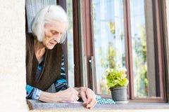 Contrôle de retraite de signature de femme supérieure à la maison Photo stock