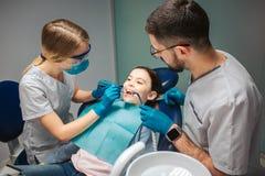 Contrôle femelle de dentiste vers le haut des dents de la fille Stad masculin d'aide à coté La fille s'asseyent dans la chaise de image libre de droits