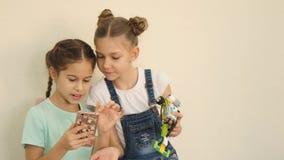 Contrôle gentil de deux filles s'ils faisaient le bon selfie avec les topys électroniques construits au mouvement lent de leçon d clips vidéos