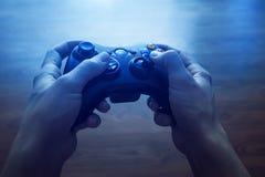 Contrôleur de jeu vidéo dans des mains humaines, devant la TV photographie stock