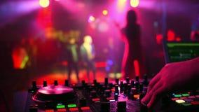 Contrôleur de mélangeur avec des mains du DJ dans la boîte de nuit avec la silhouette brouillée du chanteur de fille de danse clips vidéos