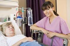 contrôlant la patiente d'infirmière vers le haut Photographie stock libre de droits