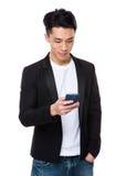 Contrôle asiatique d'homme l'email sur le téléphone portable Image stock