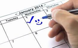 Contrôle bleu avec le sourire. Marque sur le calendrier au le 1er janvier 2014 Photos libres de droits