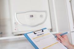 Contrôle de contrôle de plombier sur le chauffe-eau à la maison Photographie stock libre de droits