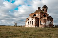 Contra la perspectiva de las nubes y del cielo azul destruyó la iglesia vieja en el pueblo fotografía de archivo